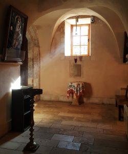 The light strikes through narrow windows into the church building